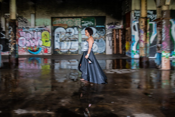 Young women walks through abandoned train station barefoot holding a champagne bottle