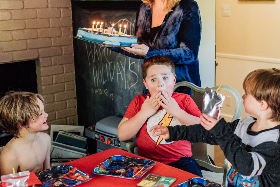 Boy holding his hands to his face as his mom brings him his birthday cake