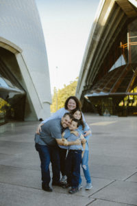 Family standing together hugging and smiling at the camera in Sydney, Australia