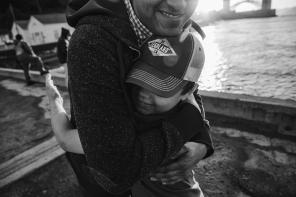 Young boy hugging uncle in front of the Golden Gate Bridge in San Francisco, CA