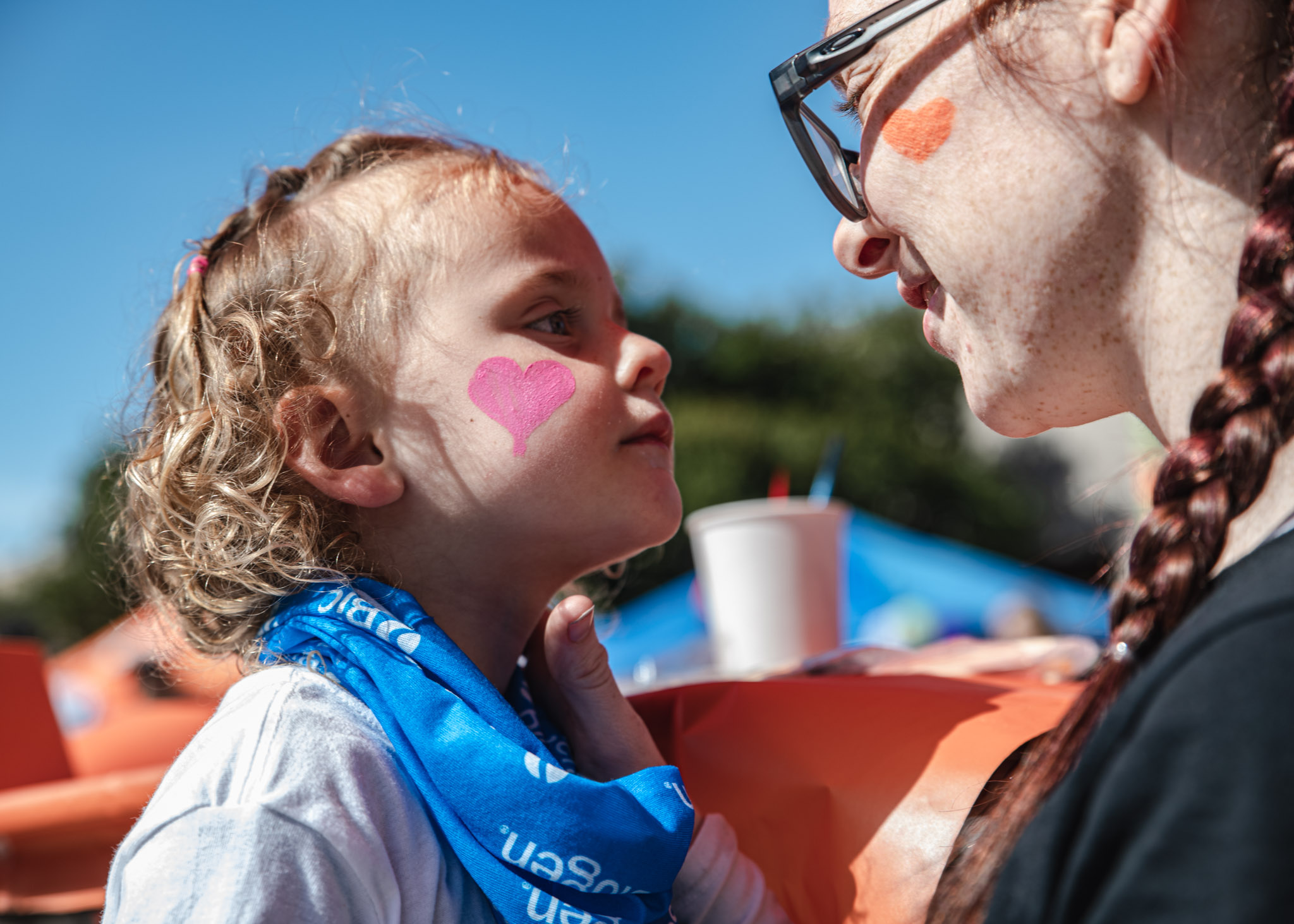 Young girl with pink heart on her cheek stares at older girl with orange heart on her cheek
