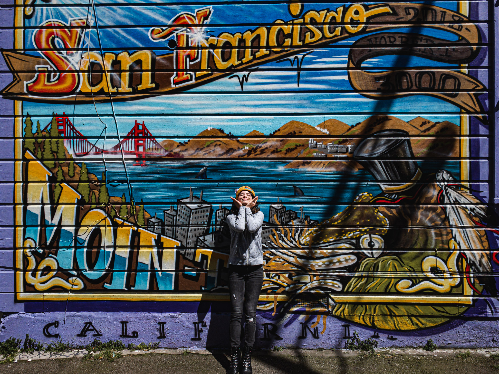 A young girl stands in front of a mural in the Mission District in San Francisco, CA