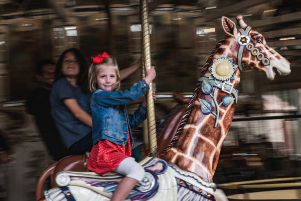 A young girl rides the Carousel at Koret Playgound in Golden Gate Park San Francisco, CA