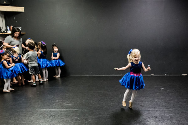 A young girl dances away from her ballet class after receiving a lollipop during a Family photography session in Anaheim, CA