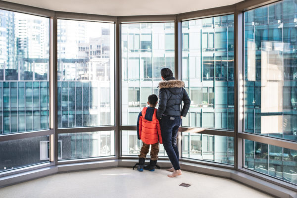 A mother and son stand in front of large windows during a San Francisco Family Photography Session in San Francisco, CA