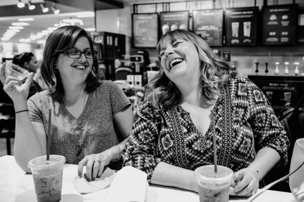 Two moms laugh together during a Family Photography Session in Anaheim, CA