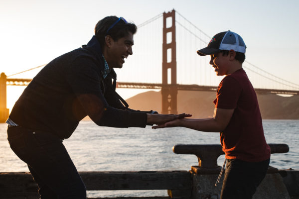 A father and son play slaps underneath the Golden Gate Bridge during a San Francisco Family Photography Session in San Francisco, CA