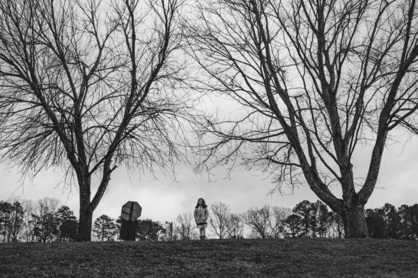 A young girl stands at the top of the hill between two giant trees during an Atlanta Family Photography session in Ball Ground, GA