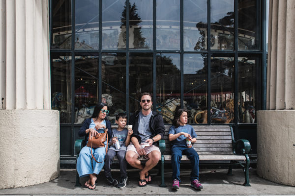 A family rests on the bench in front of a carousel during a San Francisco Family Vacation Photography session in Golden Gate Park