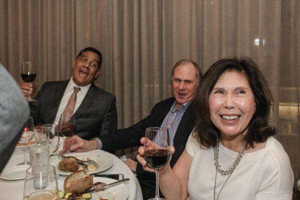 Guests cheers wine and share a laugh at the NCCA retirement dinner at John's Grill in San Francisco