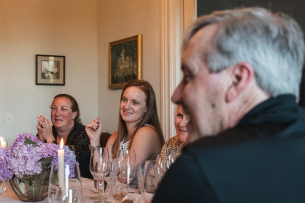 Guests sit around dinner table at Salvestrin Winery in St. Helena, CA Napa Valley
