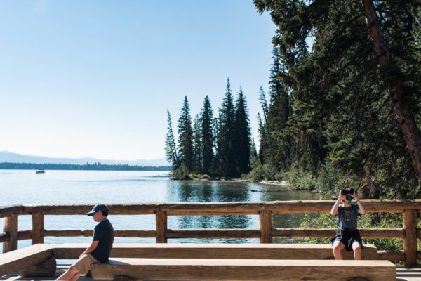 Two children sit on dock looking bored next to lake