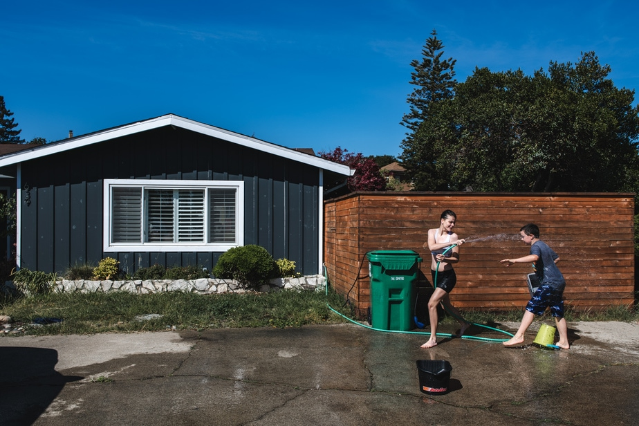 Two children engage in a water fight in front of their home in Alameda, CA