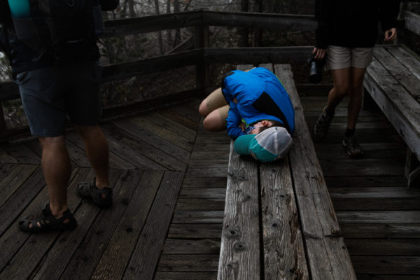 A young boy lays down on a bench to rest while his family waits for him in Yellowstone National Park