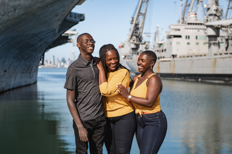 Family laughs in front of naval ships in Alameda, CA