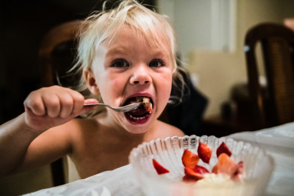 A young girl eats cake in Los Angeles, CA