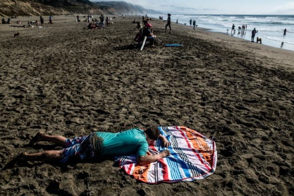 A boy lays on the beach at Fort Funston in San Francisco, CA
