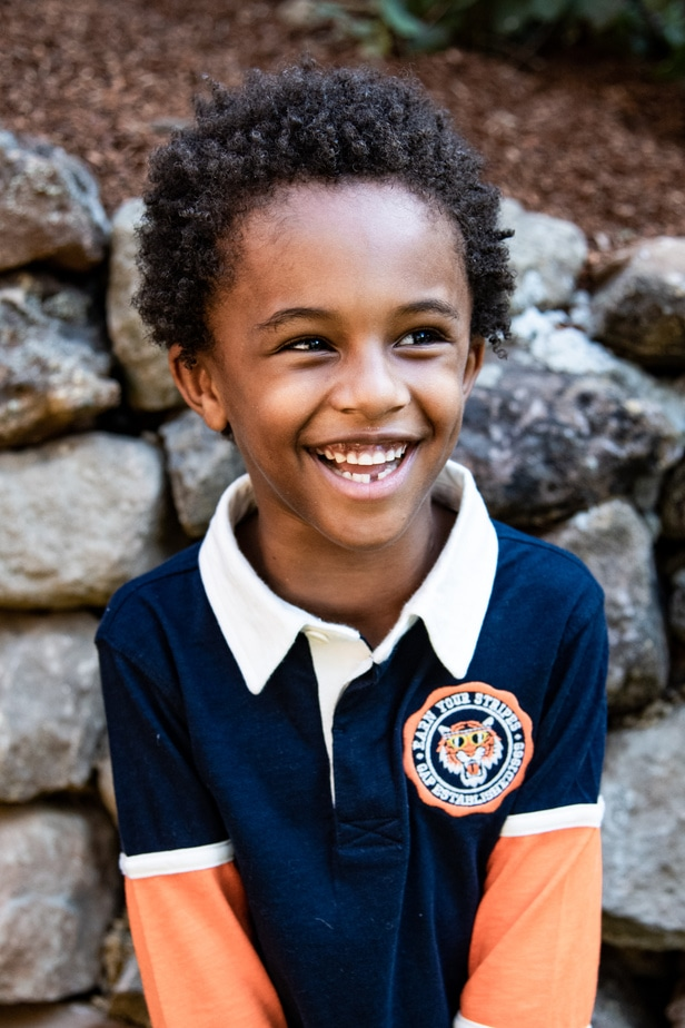 A young boy stands in front of a rock wall during school portraits in Oakland, CA