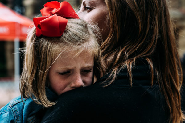 A mother holds her daughter while she is upset during a documentary family photo shoot in San Francisco, CA