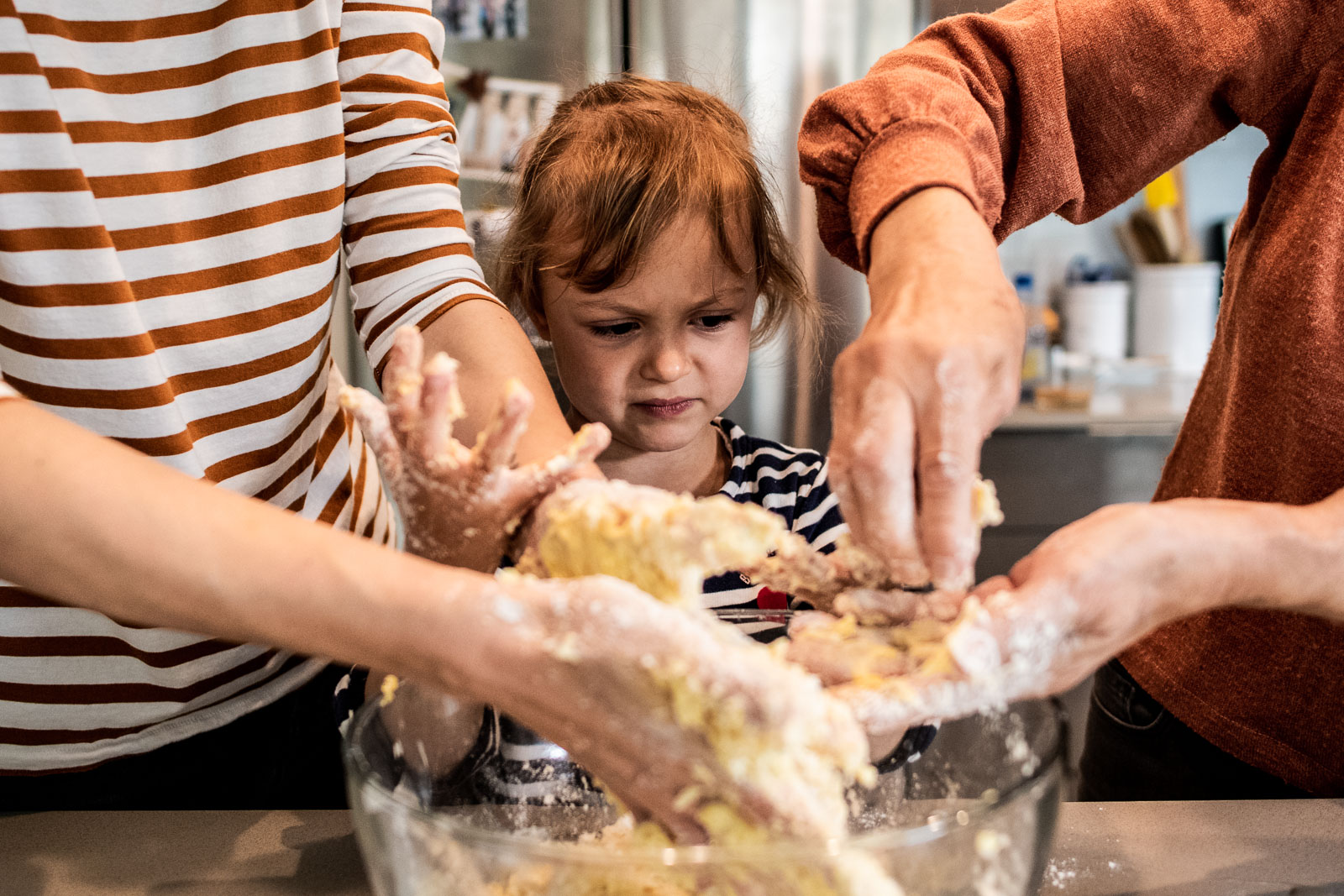 A young girl looks at her hands while baking with her mom and grandma in Berkeley, CA