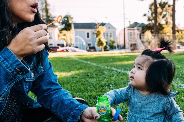 A mother blows bubbles with her daughters at the park in Alameda, CA