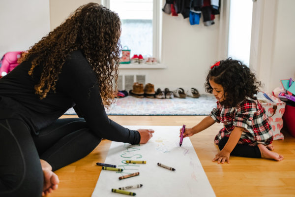 A mother draws with her daughter during a documentary family photography session in San Francisco, CA