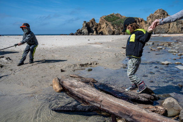 A mom helps her son across a log at Pfeiffer Beach in Big Sur, CA