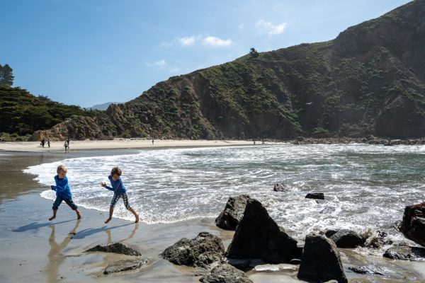 Children run away from the waves at Pfeiffer Beach in Big Sur, CA