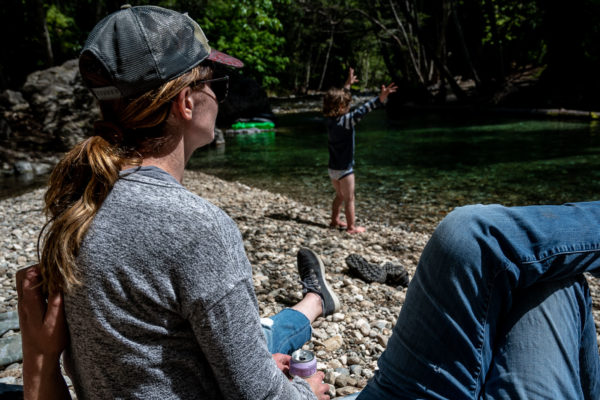 A mom watches her son throw rocks in the river at Pfeiffer State park in Big Sur, CA