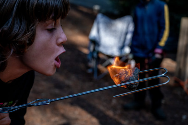A young boy blows out a marshmallow that he has roasted while camping at Ventana Campground in Big Sur, CA