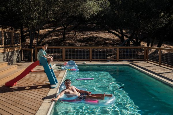 Two boys lounge in a pool in Sonoma, CA