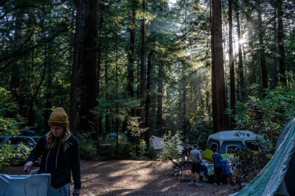 A mom cooks dinner while camping at Ventana Campground in Big Sur, CA