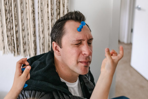 A dad closes his eyes while his daughter sticks things on his forehead in Berkeley, CA
