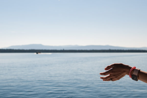 A woman holds her hand out to experience the fresh air while boating across the lake in the Grand Tetons, WY