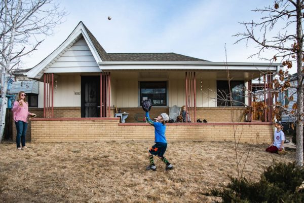 Family plays baseball in front of their house in Denver, CO
