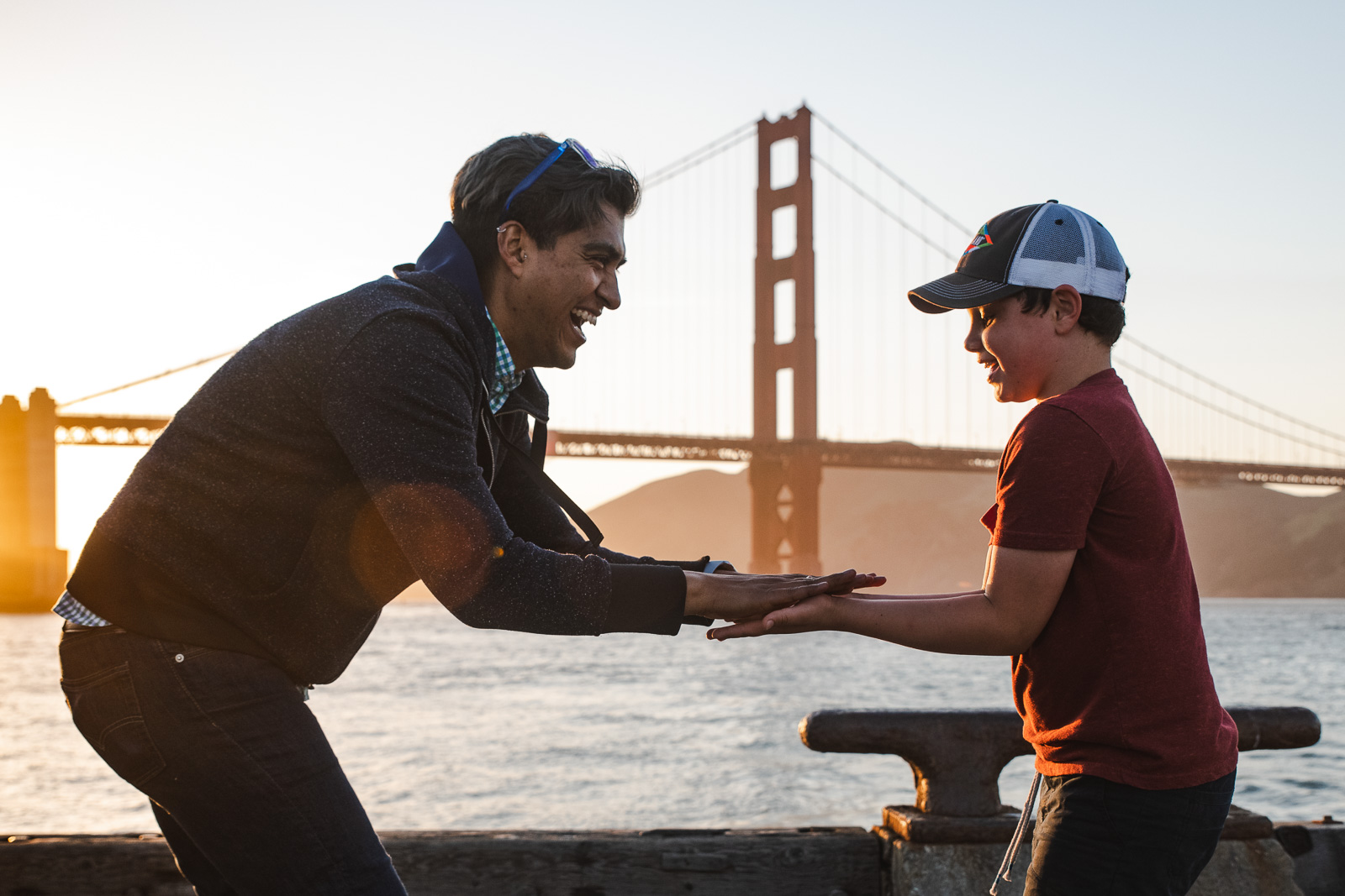 A man and young boy play slaps in front of the Golden Gate Bridge in San Francisco, CA