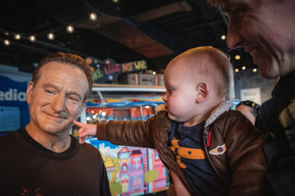 A child touches a wax figure of Robin Williams in San Francisco, CA