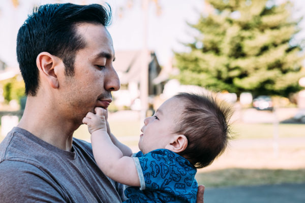 A father holds his son in a park in Alameda, CA