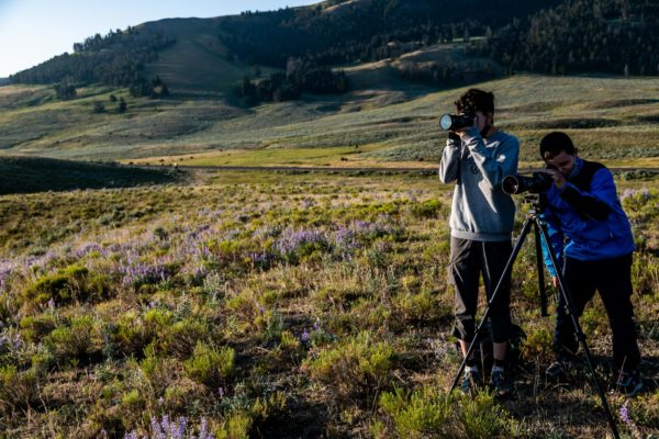 Two children look through telescopes in Yellowstone National Park