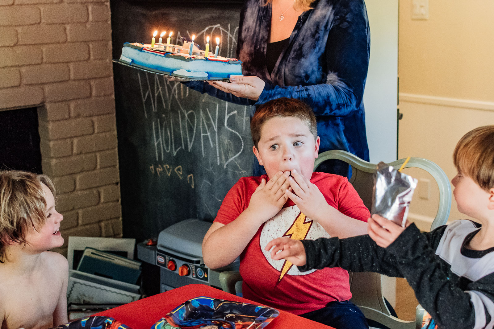 A young boy looks surprised as his mom brings out his birthday cake in Oakland, CA