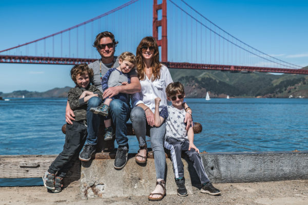 A family poses in front of the Golden Gate Bridge in San Francisco, CA