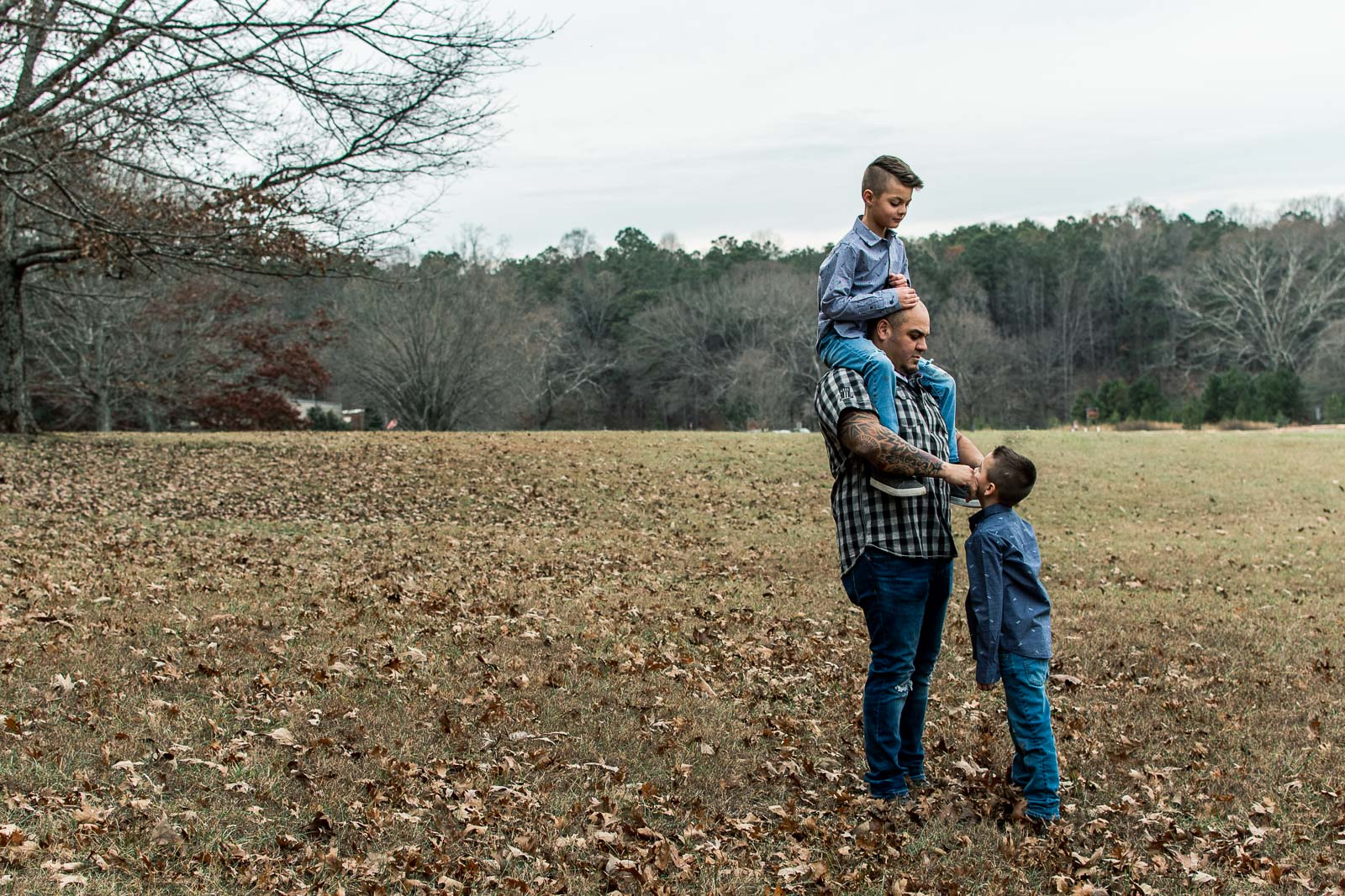 A father plays with his sons at the park in Kennesaw, GA