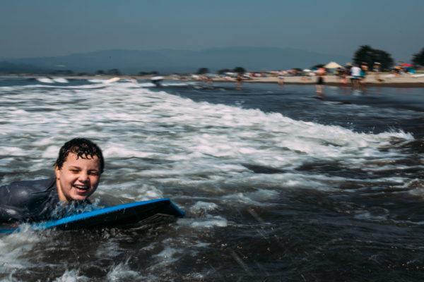 A boy smiles as he boogie boards in Stinson Beach, CA