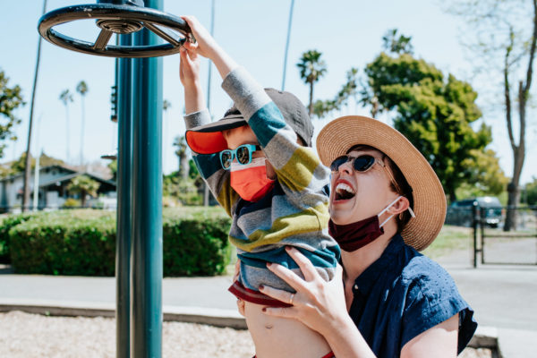 A mom laughs with her boy on playground equipment in Washington Park, Alameda, CA