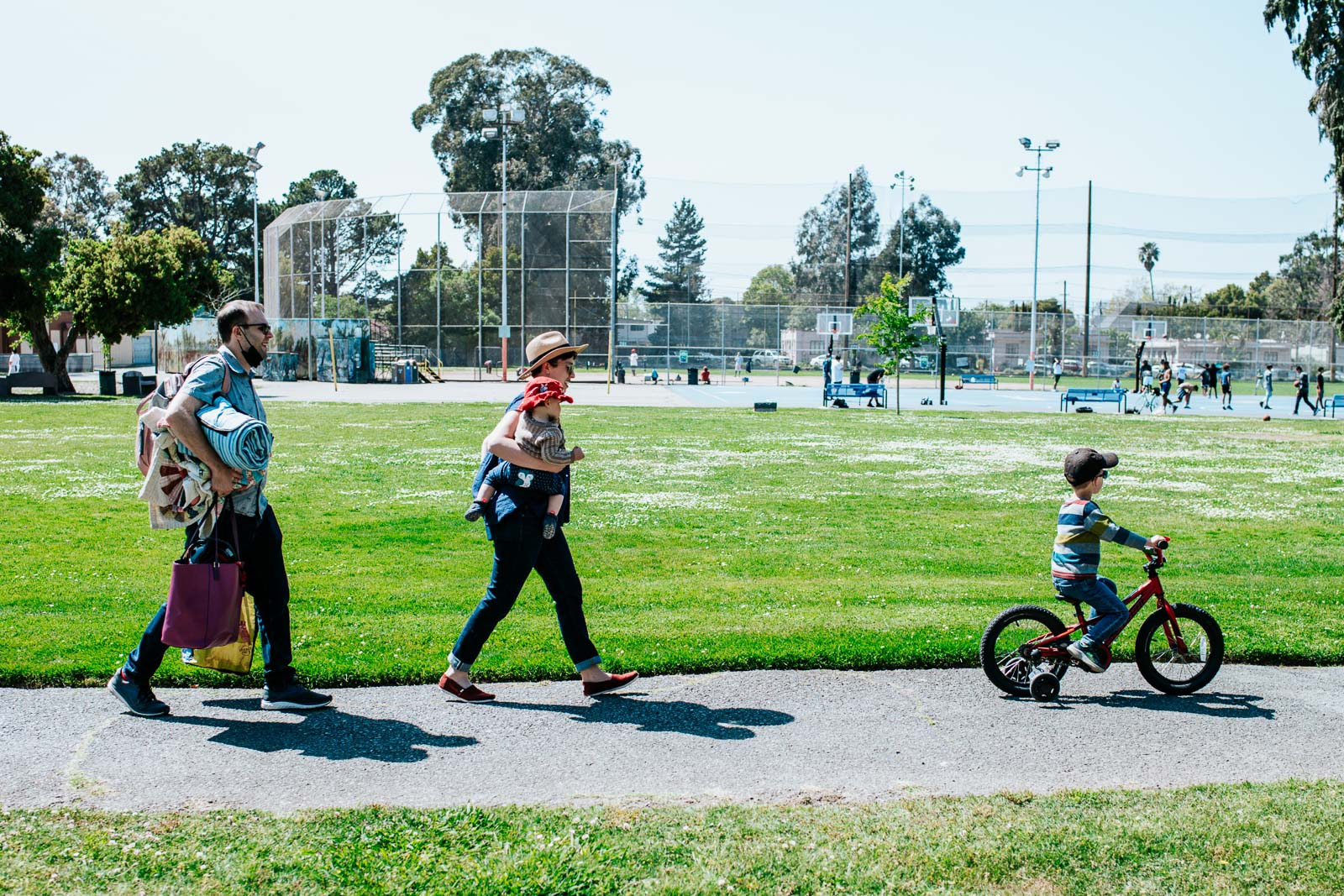 A family works through Washington Square Park in Alameda, CA