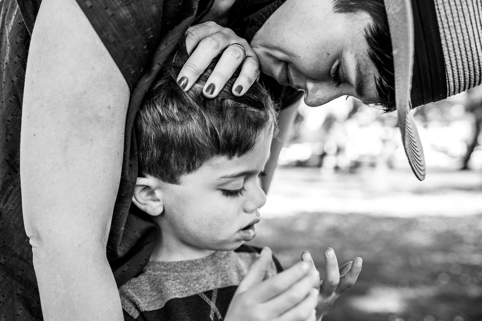 A mom comforts her son while he looks at his hand at Washington Square Park in Alameda, CA
