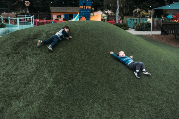 Two boys play on a hill in Children's Fairyland in Oakland, CA
