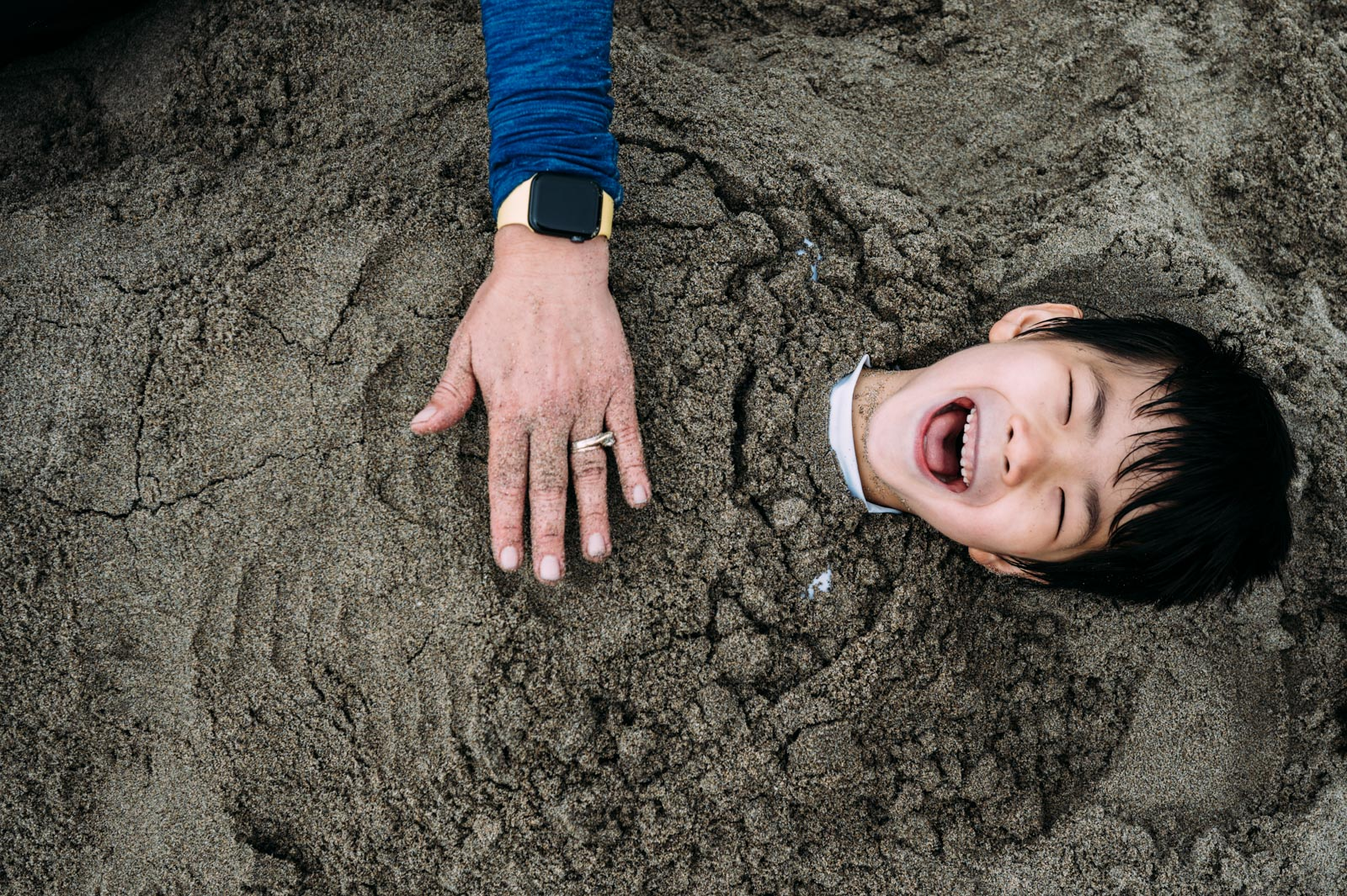 Boy laughs while he is buried in the sand by his mom in Santa Cruz, CA