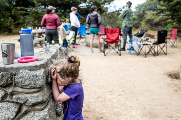 A young girl plays hide n seek while camping at Sunset State Beach in Santa Cruz, CA